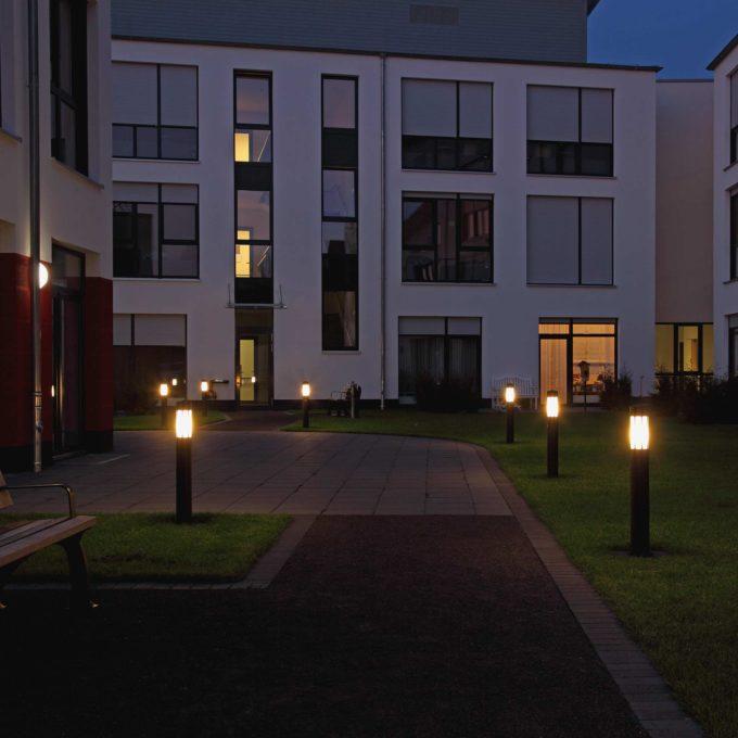 Der Innenhof eines Mehrfamilienhauses wird in der Abenddämmerung beleuchtet