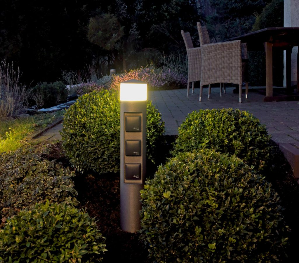 Eine Steckdosensäule mit integrierter Leuchte steht in einem Terrassenbeet