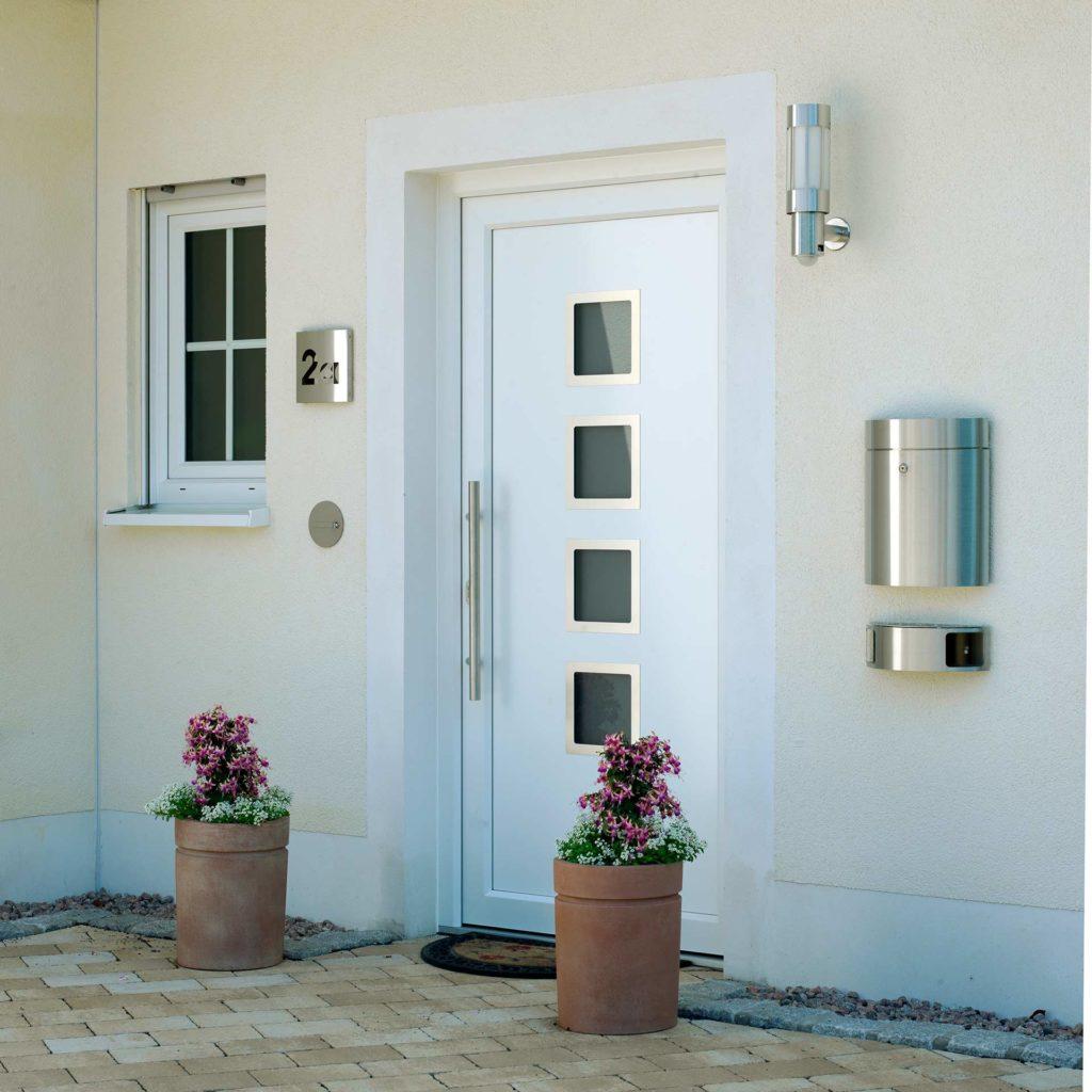 Ein harmonisch gestalteter Hauseingang mit Pflanzkübeln, Edelstahl-Briefkasten und Leuchten