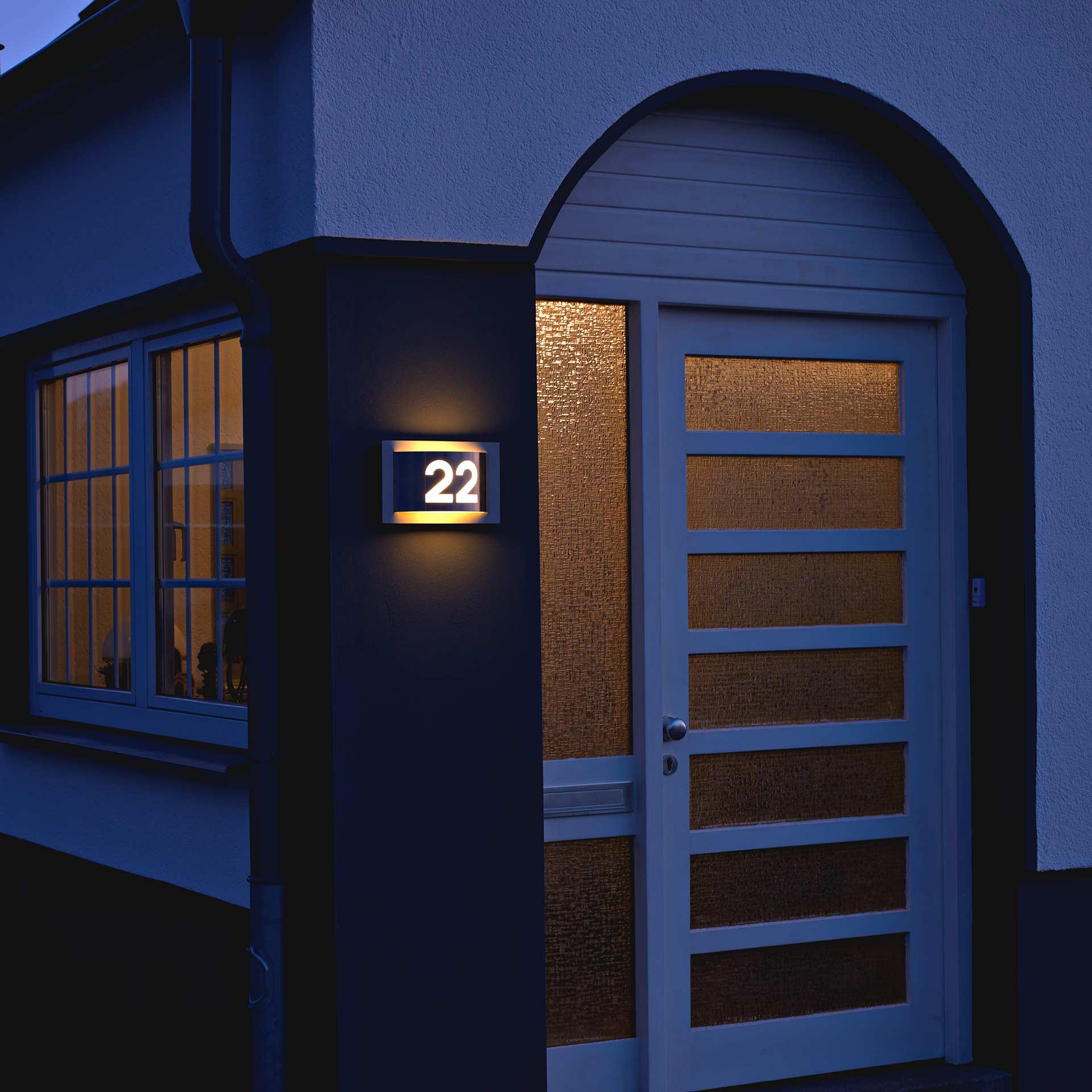 Ein bogenförmiger Hauseingang inklusive Wandbeleuchtung