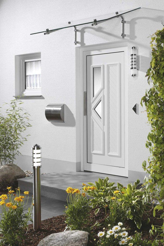 Eine moderne Haustür mit einem Ensemble aus Briefkasten und Edelstahl-Außenleuchten