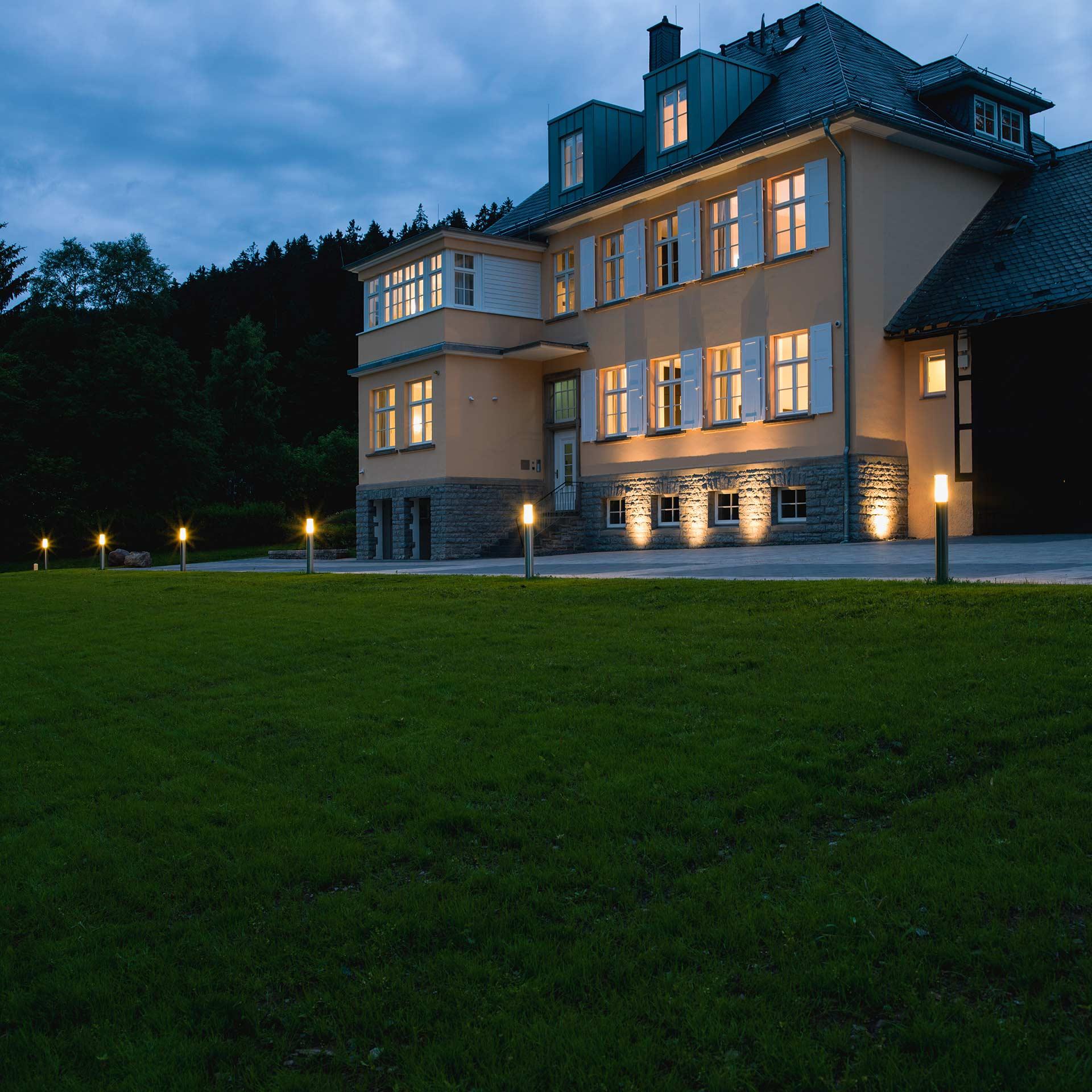 Ein großes Gutshaus wird durch mehrere Außenleuchten in der Abenddämmerung erhellt