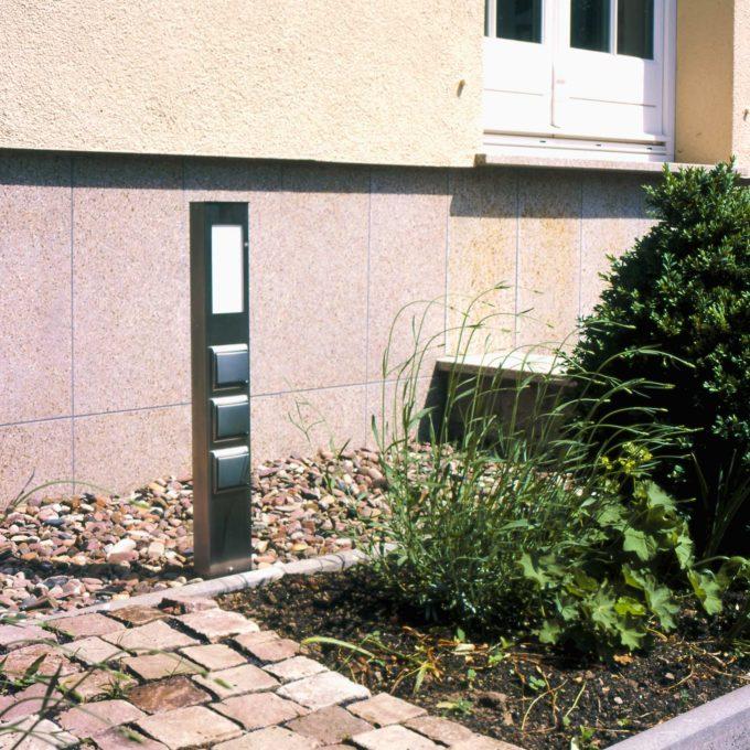 Eine beleuchtete Steckdosensäule am Sockel eines Hauses
