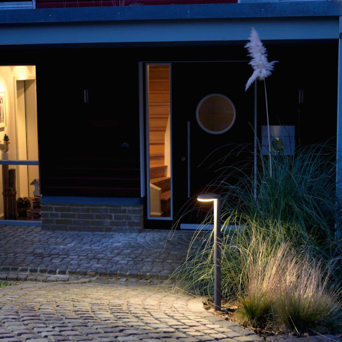 Eine LED-Pollerleuchte wirft flächiges Licht auf einen Steinweg