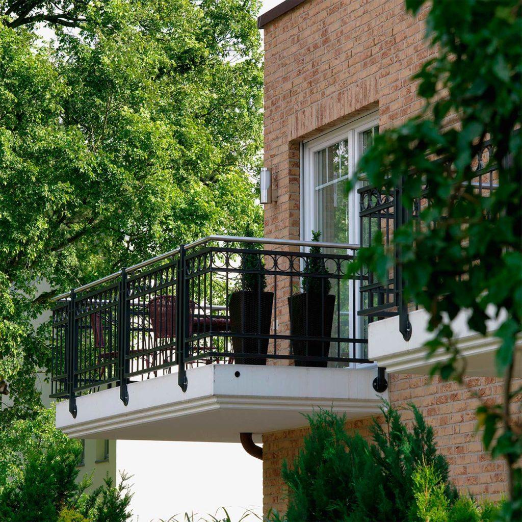 A balcony with wrought iron lattice on a brick house.