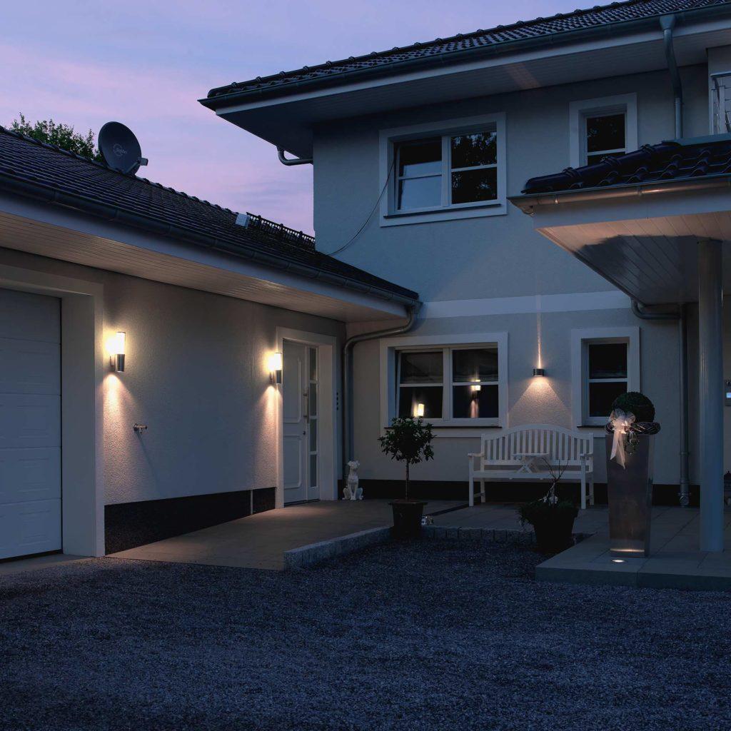 Ein gepflegter Garagenhof wird durch mehrere Leuchten stimmungsvoll erhellt
