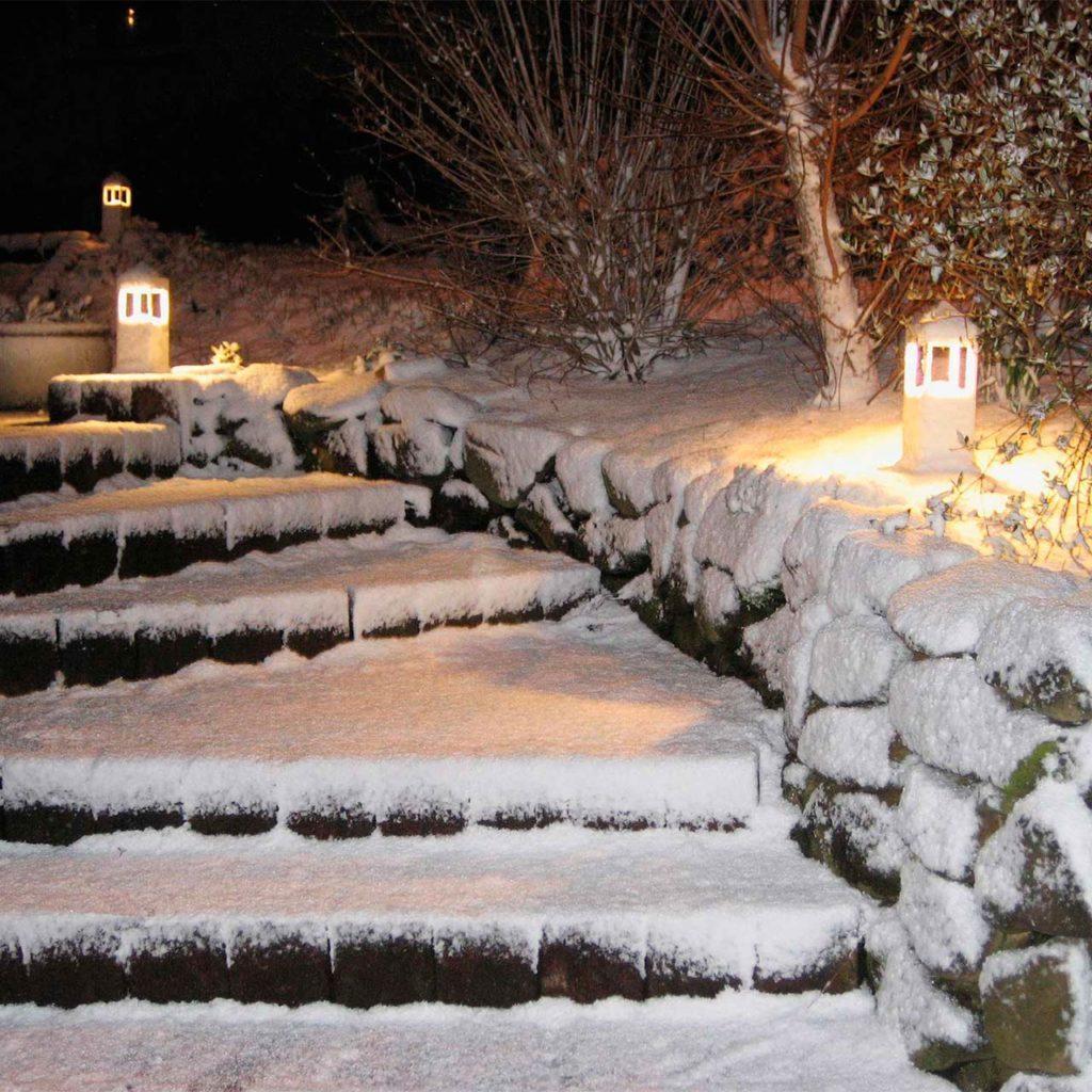 A winter snowed-in staircase illuminated with Albert bollard lights.