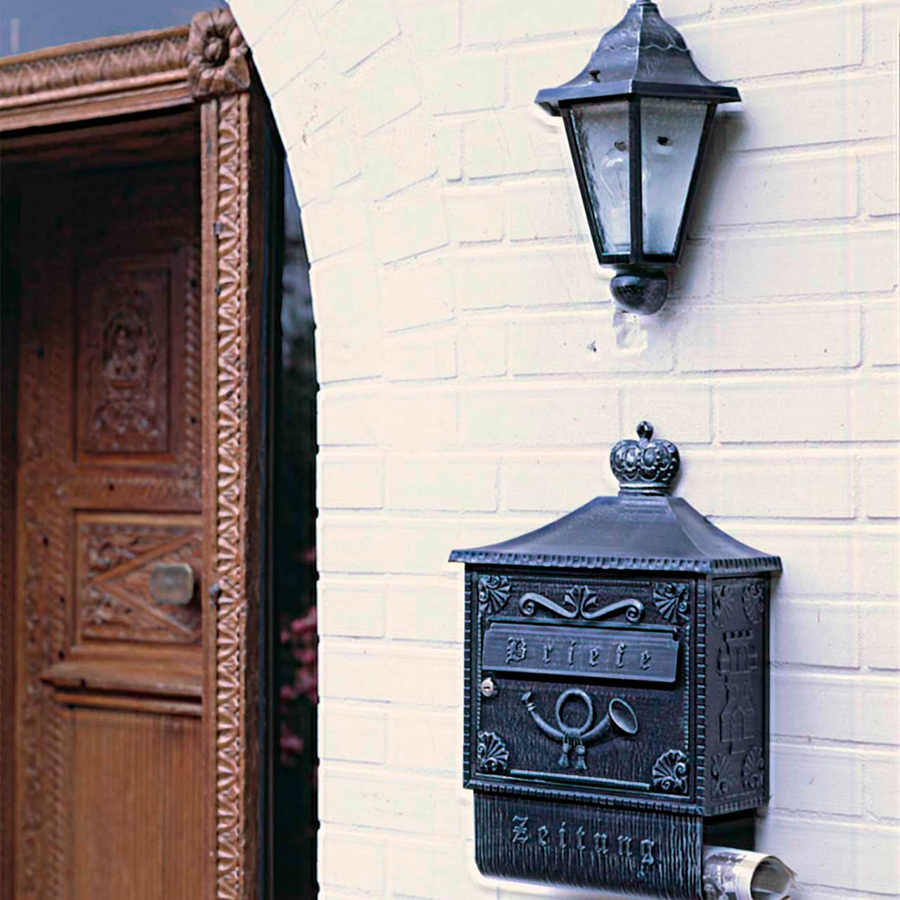 Ein englischer Wandbriefkasten mit passender Außenleuchte und Zeitungshalter