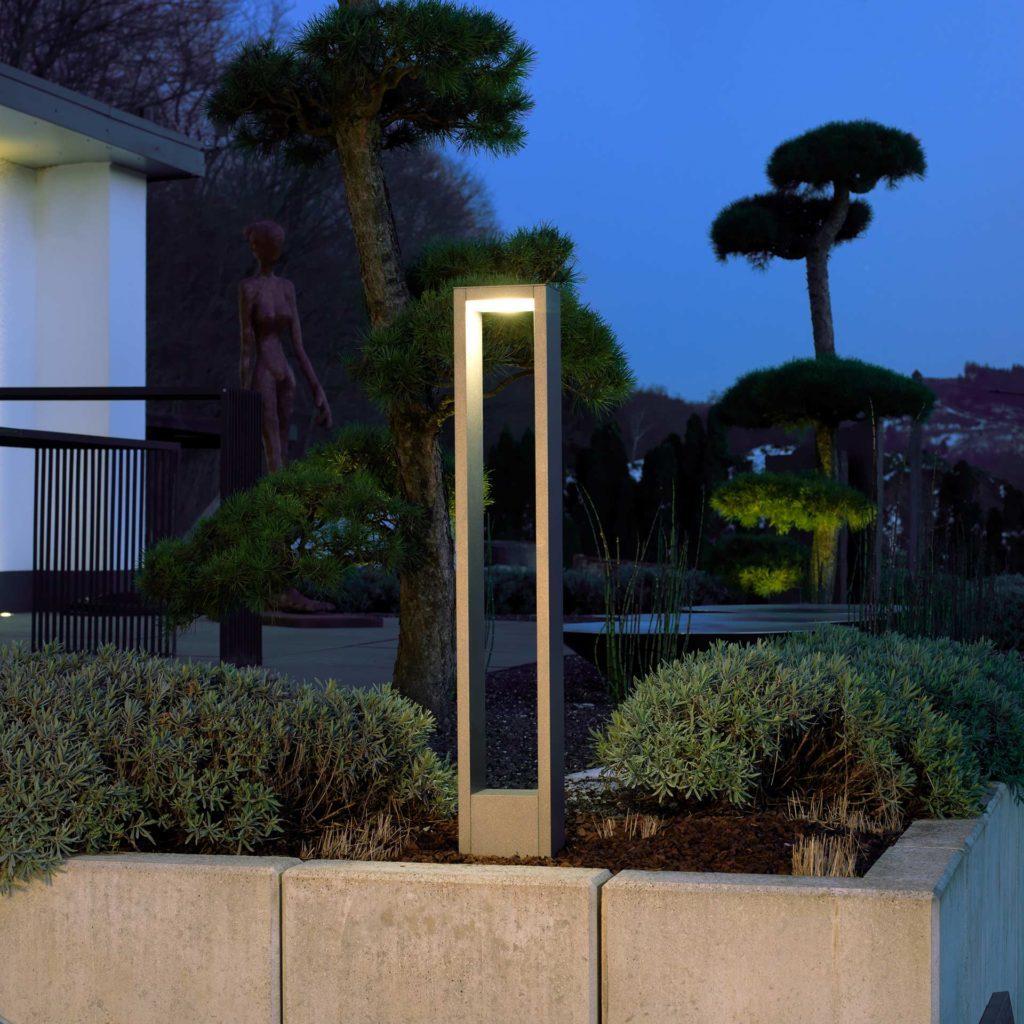 A modern light column illuminates a garden area.