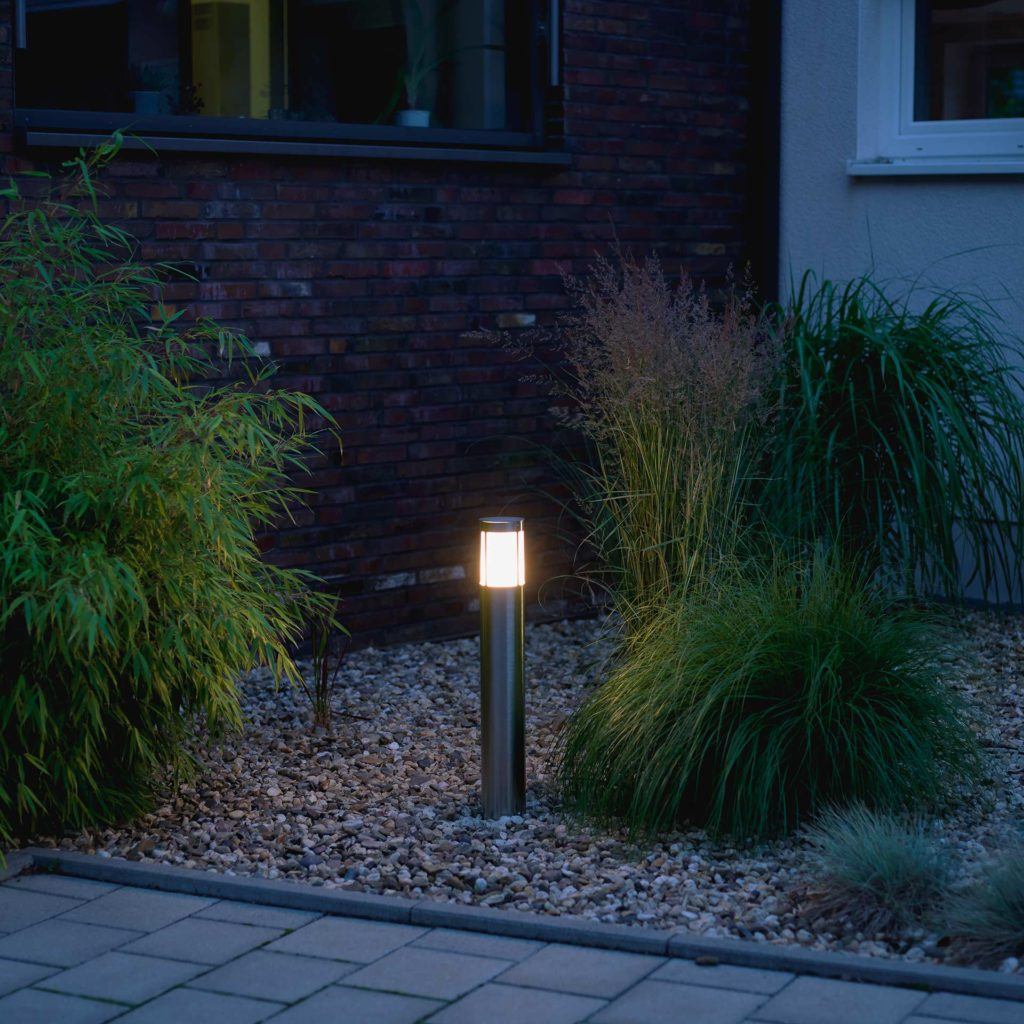 A technical high quality stainless steel pillar light provides light in a gravel bed