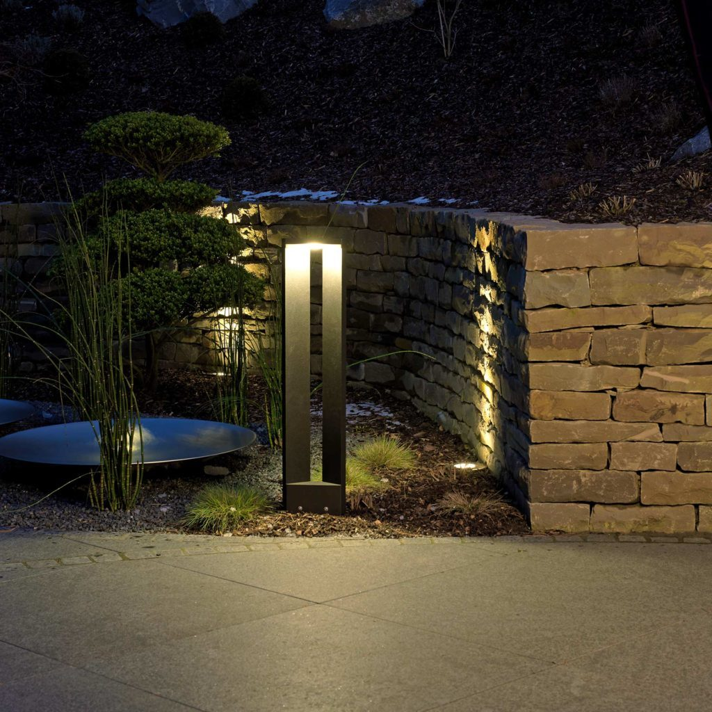 A modern path light provides cozy light on an old stone wall.