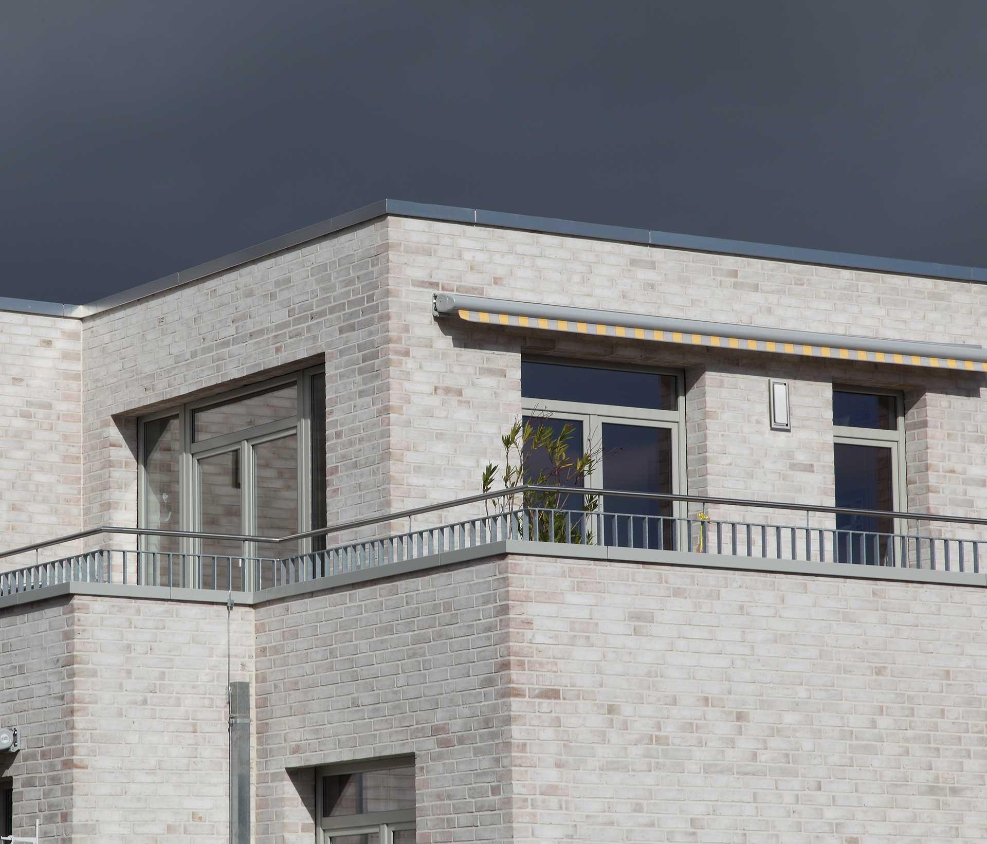 Ein modernes Wohnhaus mit eingelassenen Wandeinbauleuchten in der Hauswand