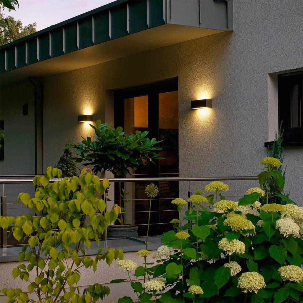Zwei Wandleuchten aus Edelstahl fungieren als moderne Balkonbeleuchtung