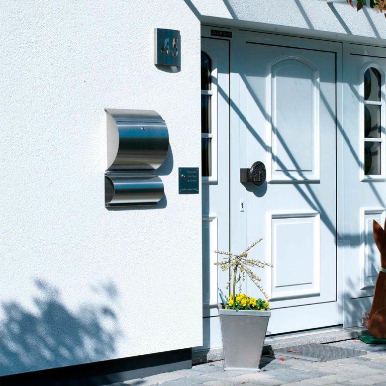 Ein moderner Edelstahl-Wandbriefkasten an einer weißen Hauswand
