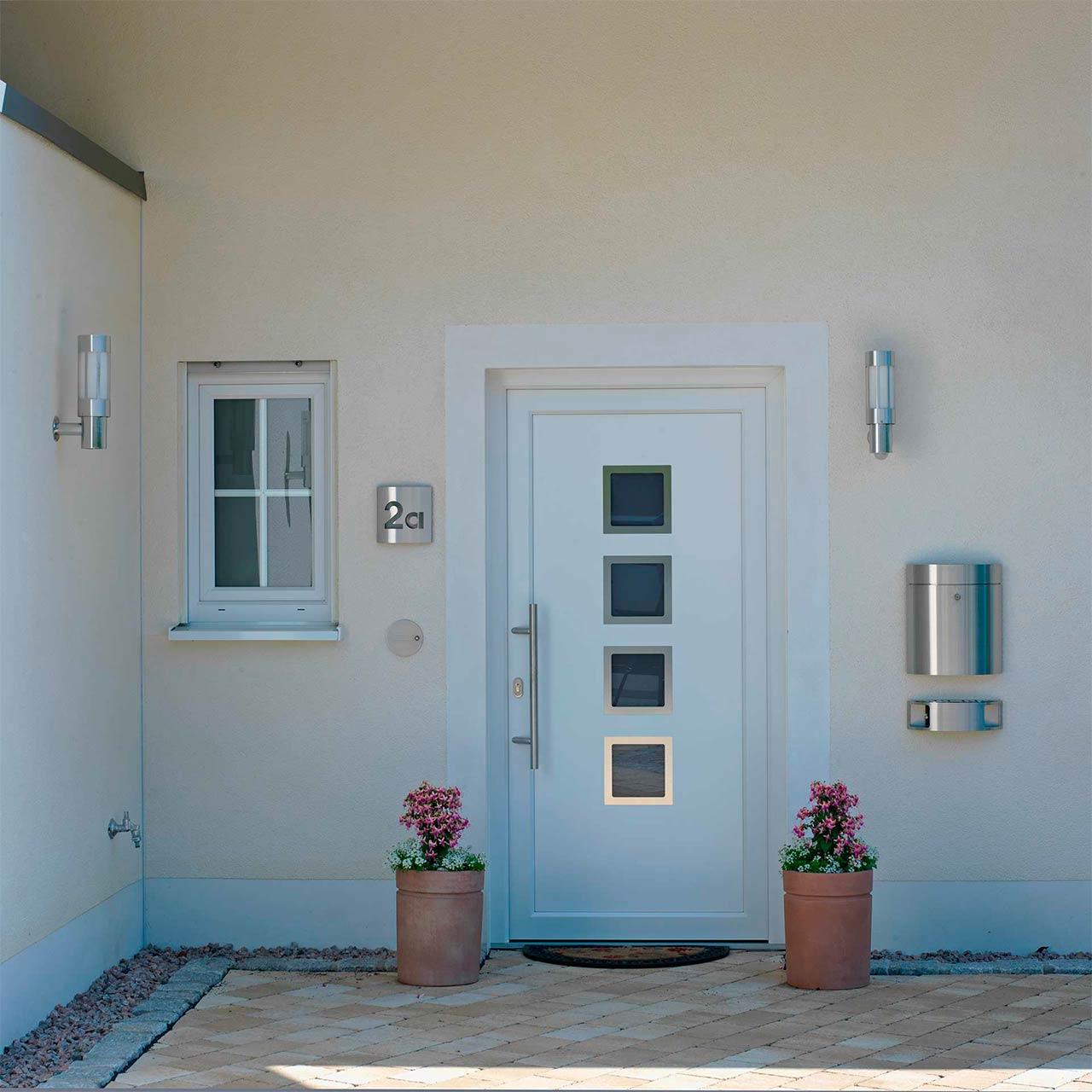 Ein weiß gestrichener Hauseingang mit Blumenkübeln, Hausnummer und Außenleuchten