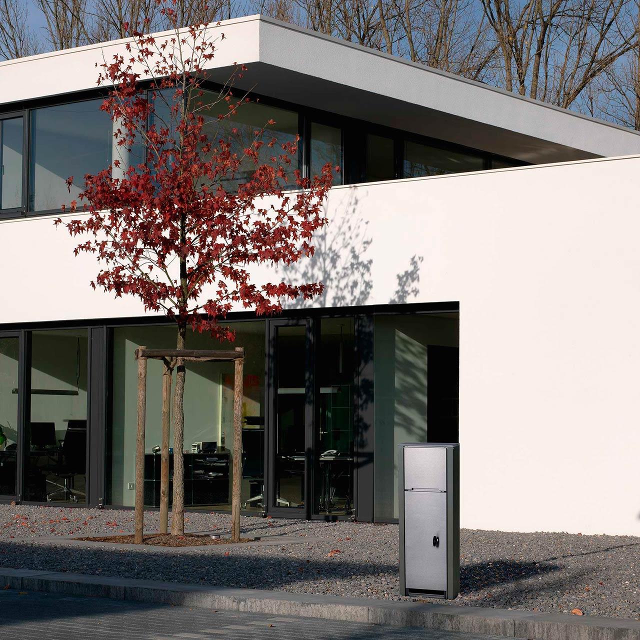Ein weißes Gebäude mit modernem Vorgarten und einer Energiesäule im Vordergrund