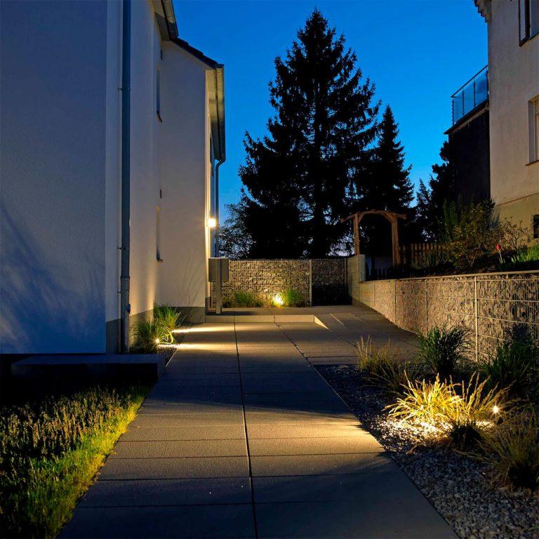 Erdspieße mit LED-Licht beleuchten einen Gehweg in der Abenddämmerung