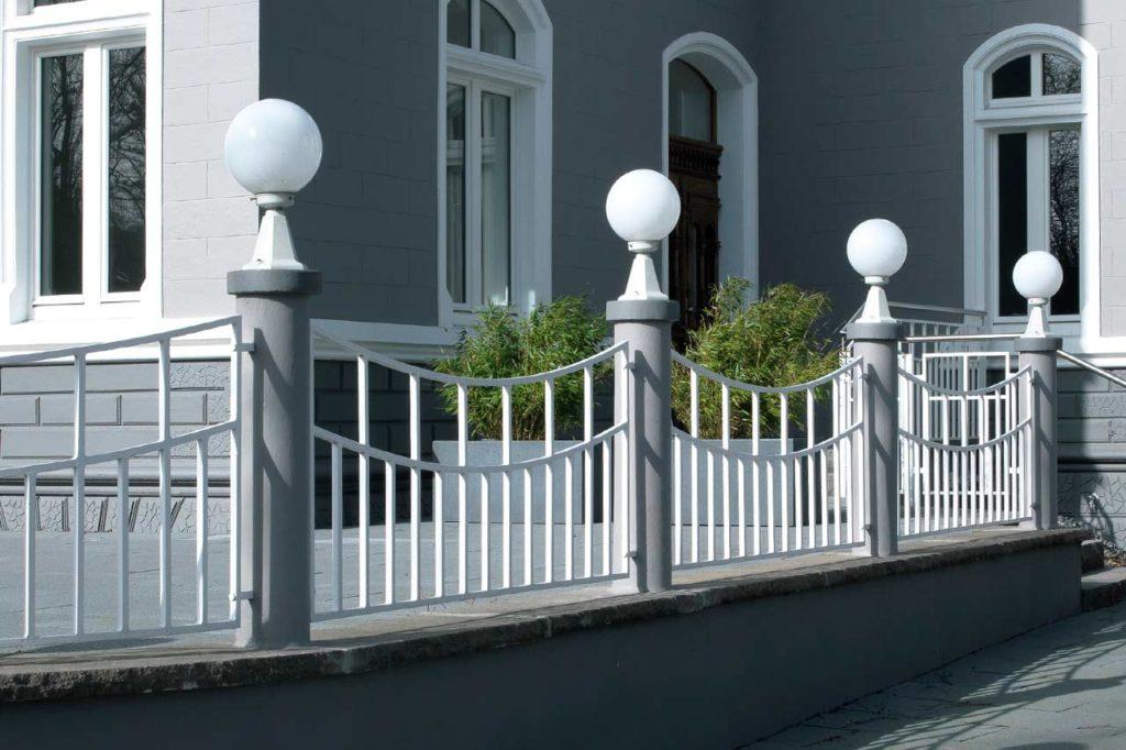 Ein schmiedeeiserner Gartenzaun von hoher Qualität, auf dem Sockelleuchten thronen