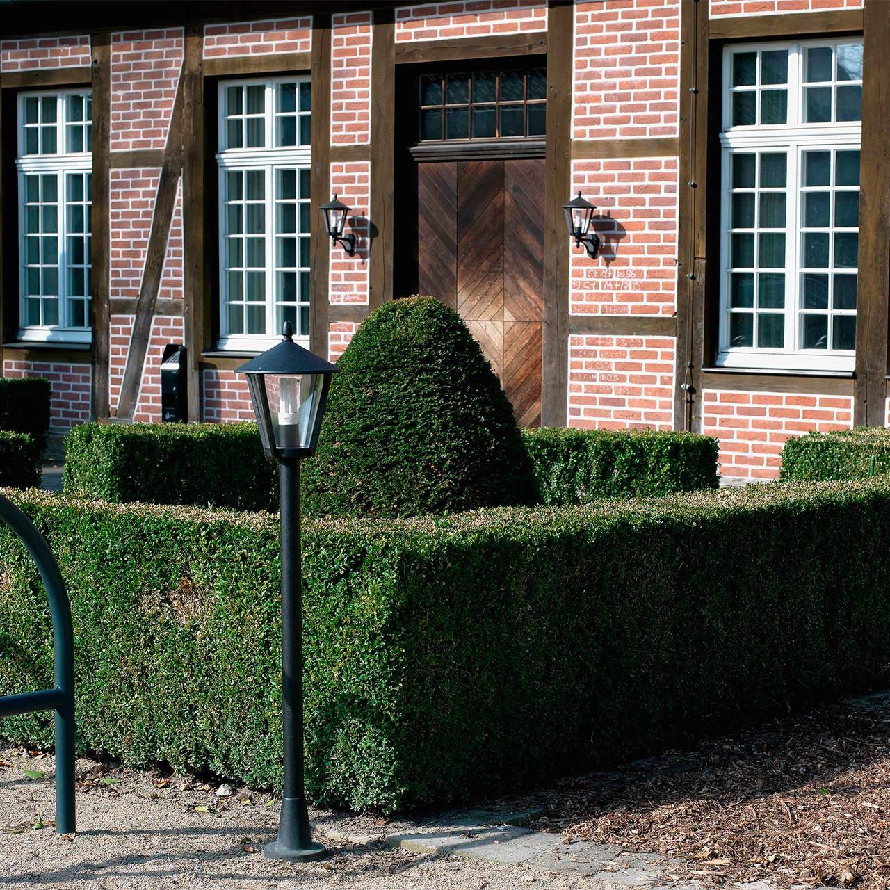 Eine Gartenanlage mit Hecke, Büschen und mittelhohen Lichtmasten
