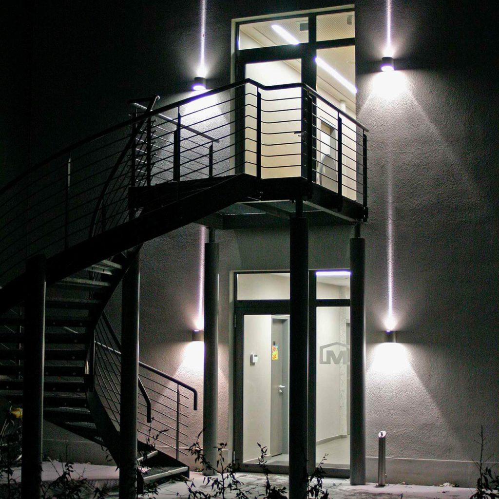 Eine winterlich verschneite Treppe, beleuchtet mit Albert Pollerleuchten.