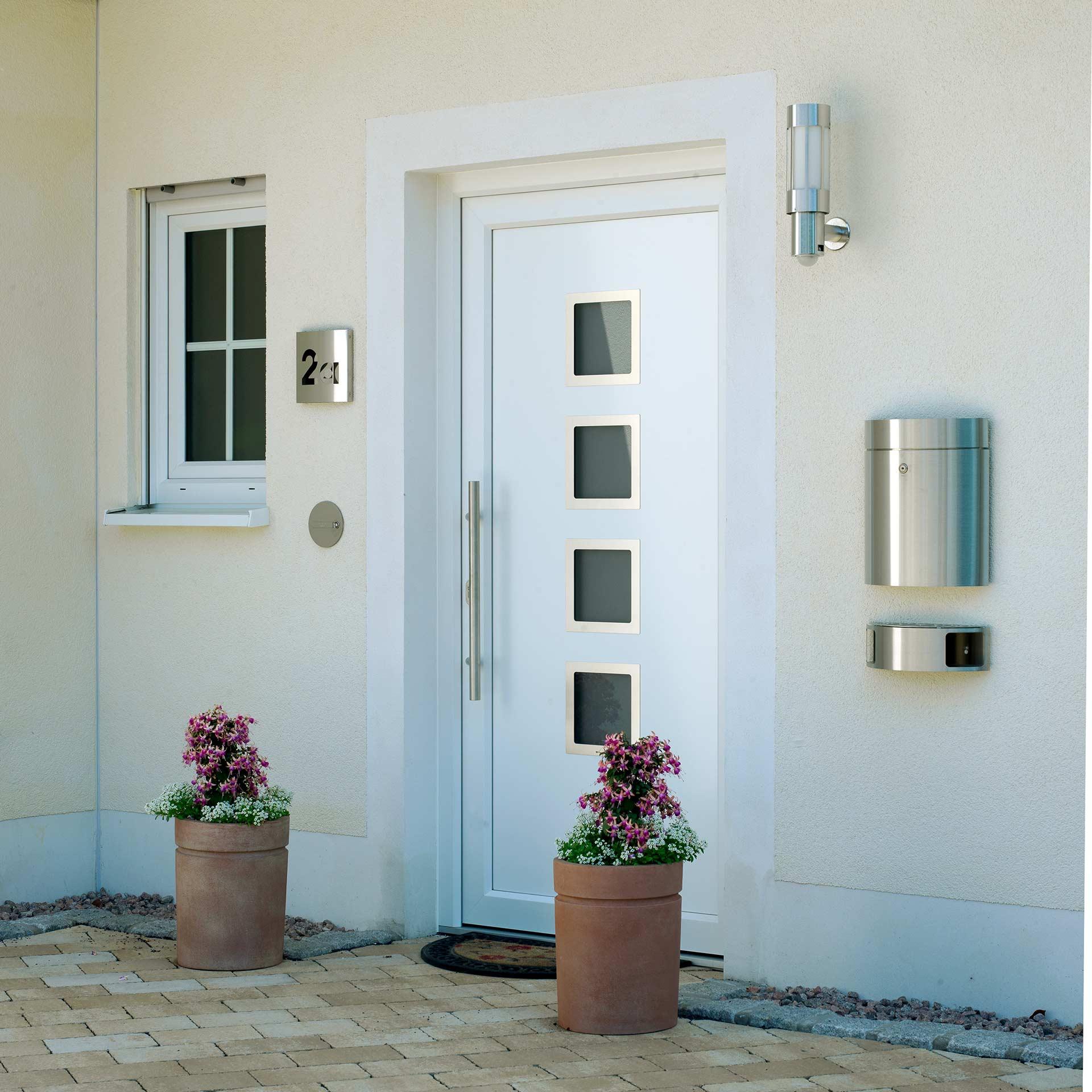 Ein harmonisch gestalteter Hauseingang mit Pflanzkübeln und Außenleuchten