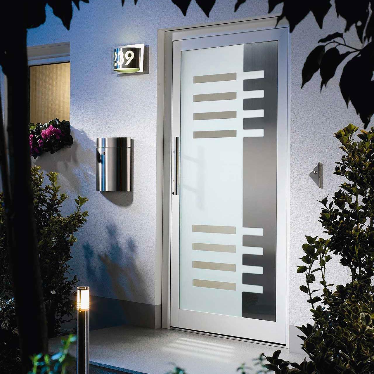 Eine moderne Haustür mit einem Ensemble aus Briefkasten, Wandleuchte und Wegeleuchte