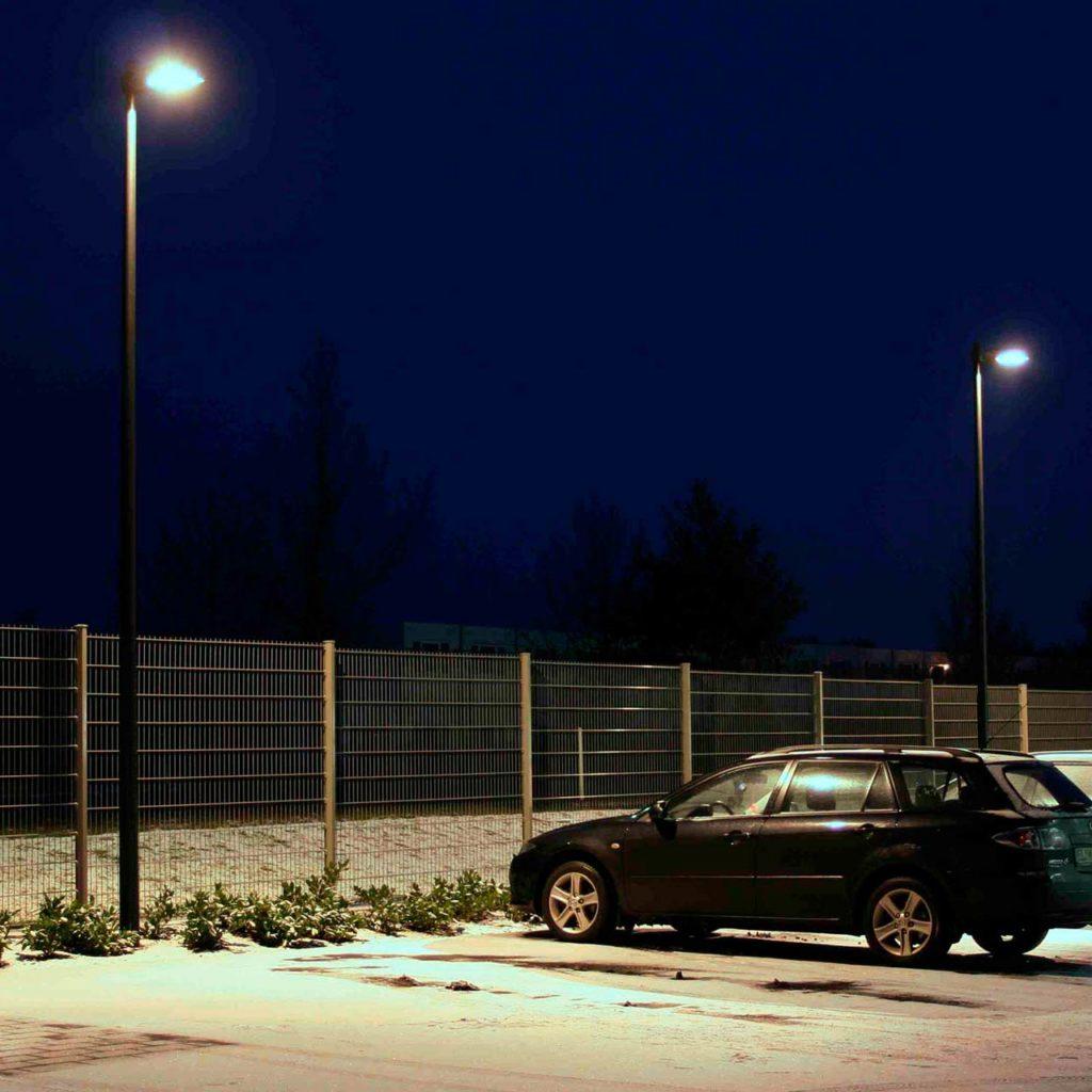 Hohe und moderne Mastleuchten stehen am Rande eines Parkplatzes.