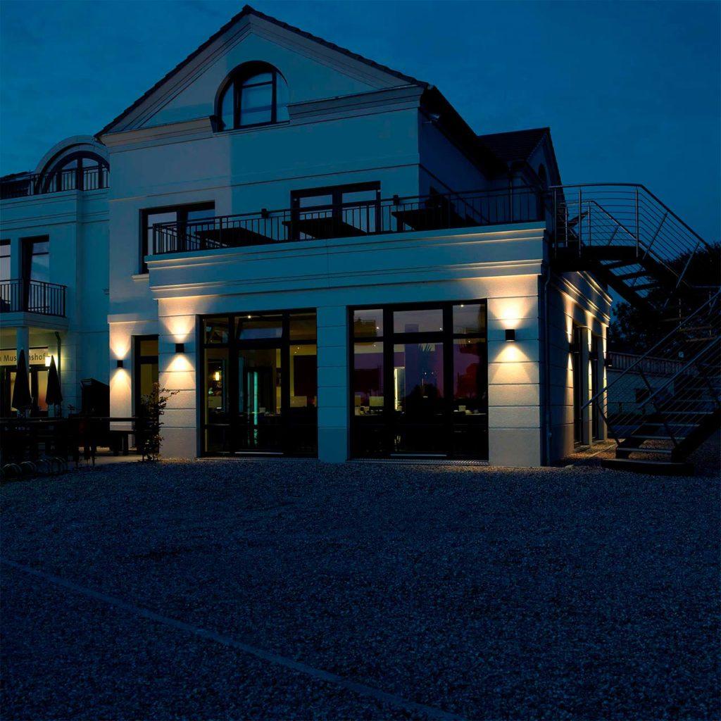 Eine Villa wird nachts von mehreren Leuchten illuminiert.