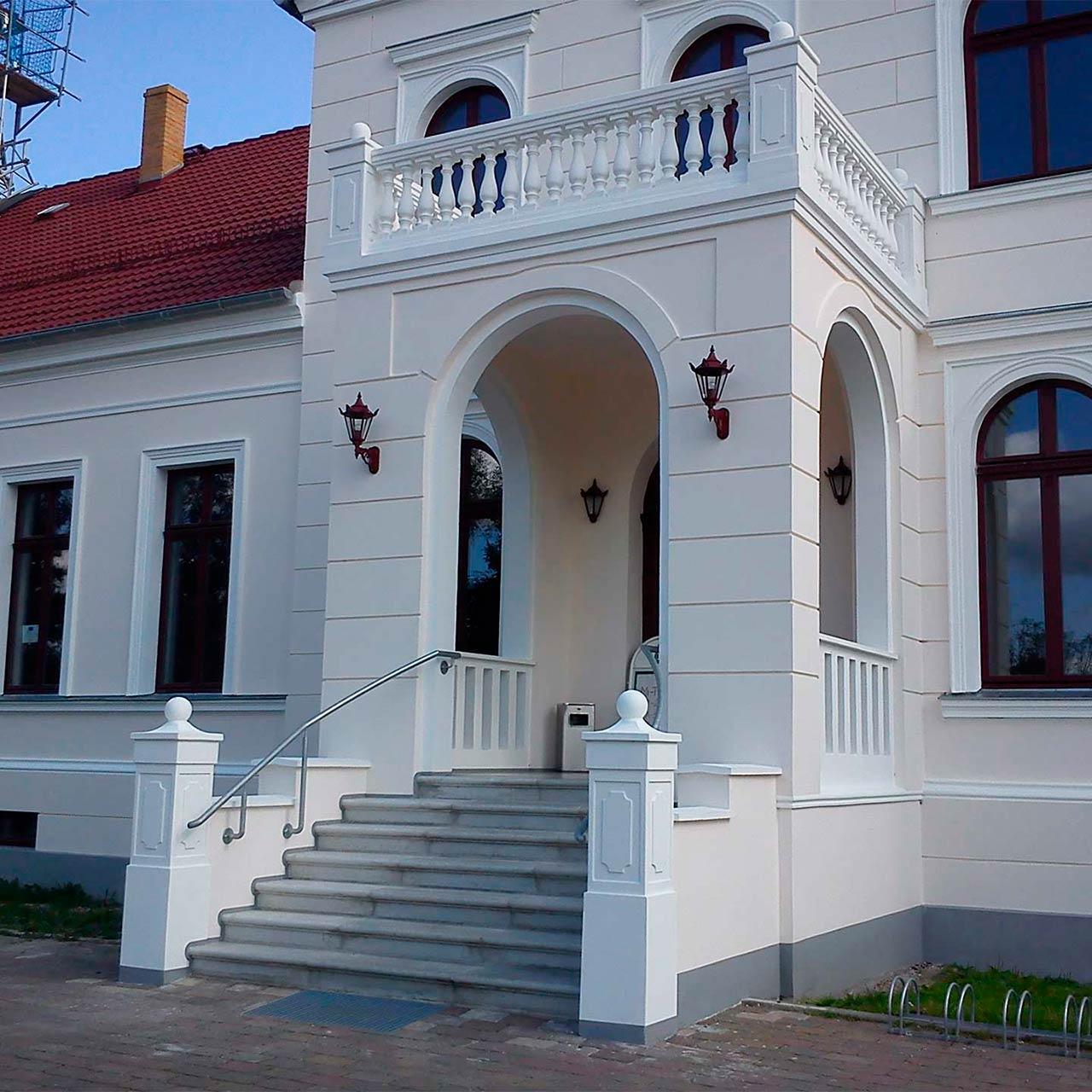 Ein Landhaus mit weißer Fassade wird von zwei Außenleuchten eingerahmt