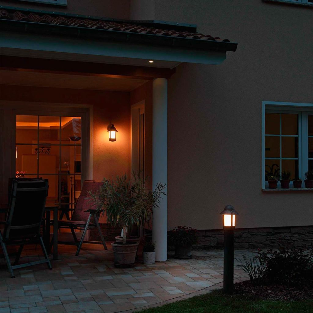 A terrace with a Mediterranean stone floor is set off by a patio lighting and a pedestal lamp.