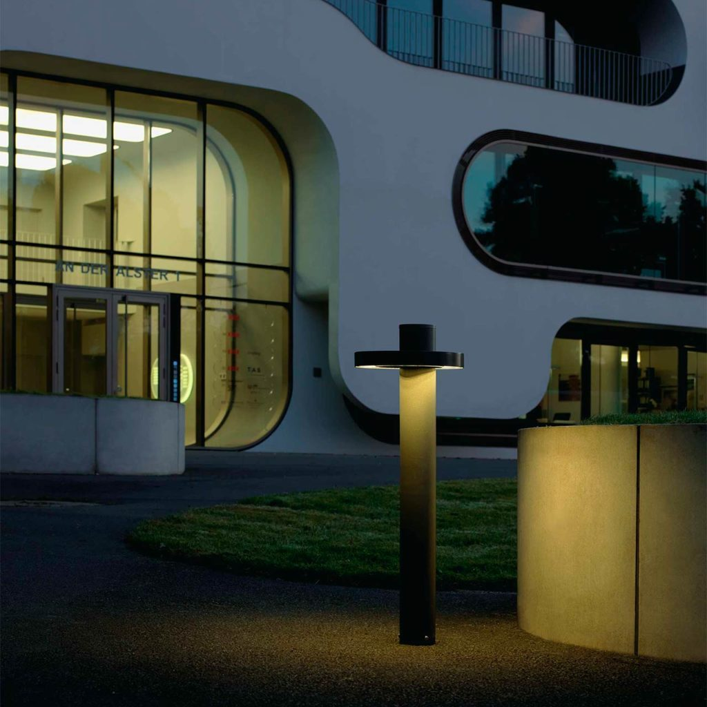 A stylish object lighting stands by a large office building.