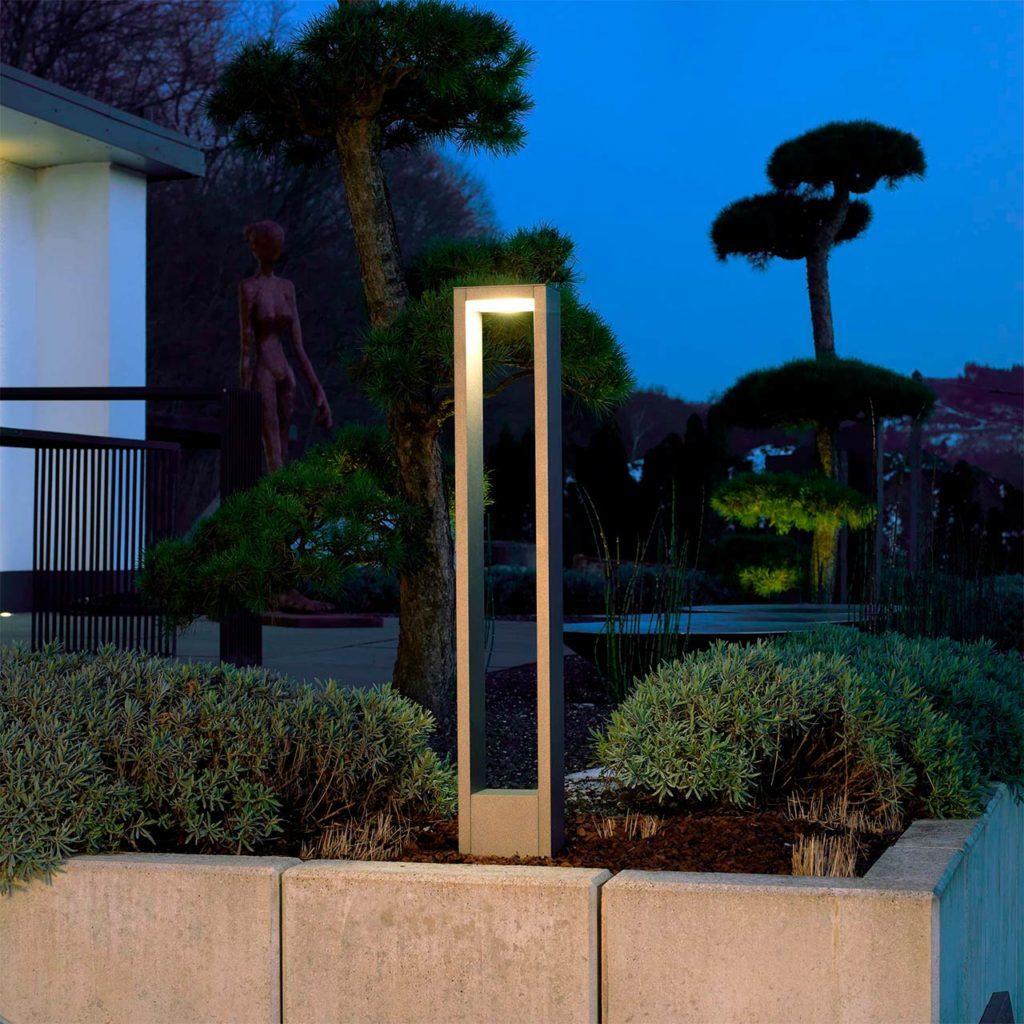 A modern garden light stands at the edge of a flower bed.