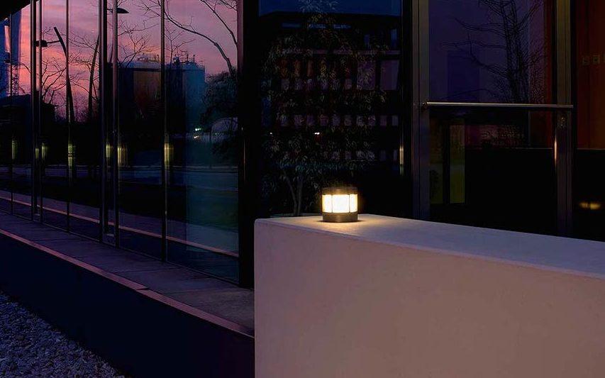 Eine kleine Sockelleuchte sorgt für malerisches Licht an einer Mauer vor einem Gebäudekomplex.