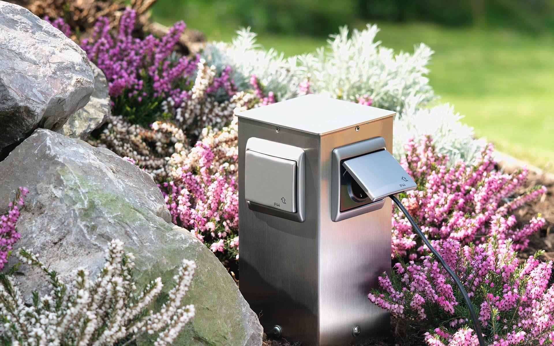 Eine dezente Steckdosensäule aus Edelstahl sorgt für Strom im Blumenbeet.