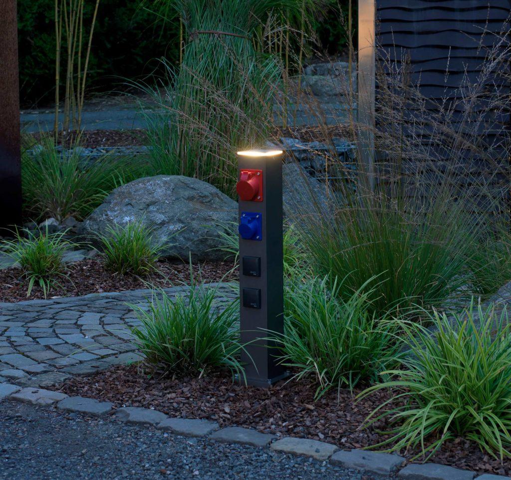 Eine Energiesäule mit verschiedenen Anschlüssen sorgt für die Energieversorgung in einem Garten.