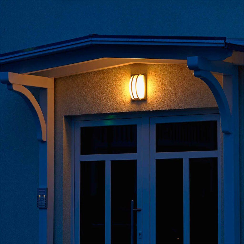 Eine einzelne Wandleuchte illuminiert einen Hauseingang