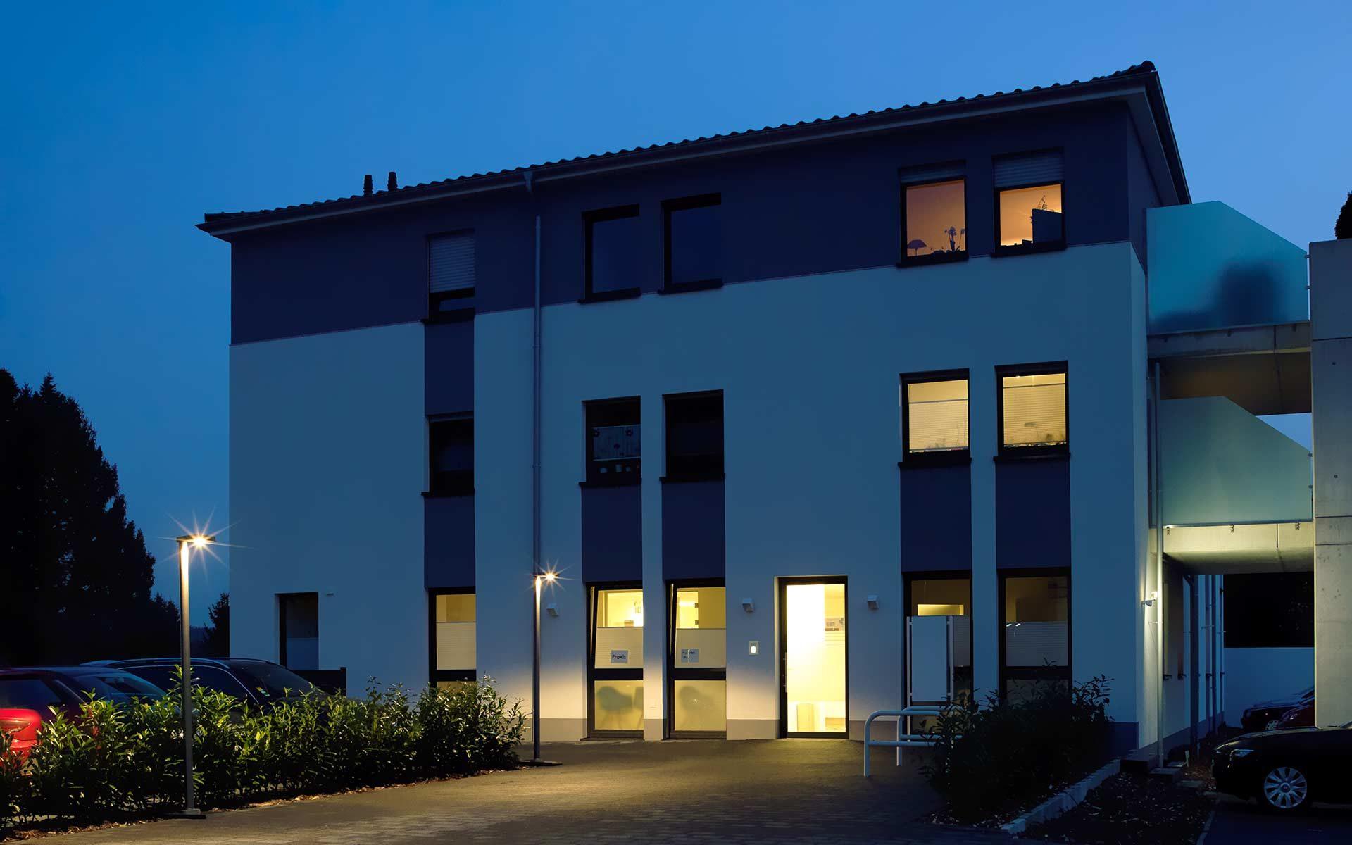 Der Gehweg, der zu einem modernen Haus führt, wird abends von mehreren Mastleuchten beleuchtet.