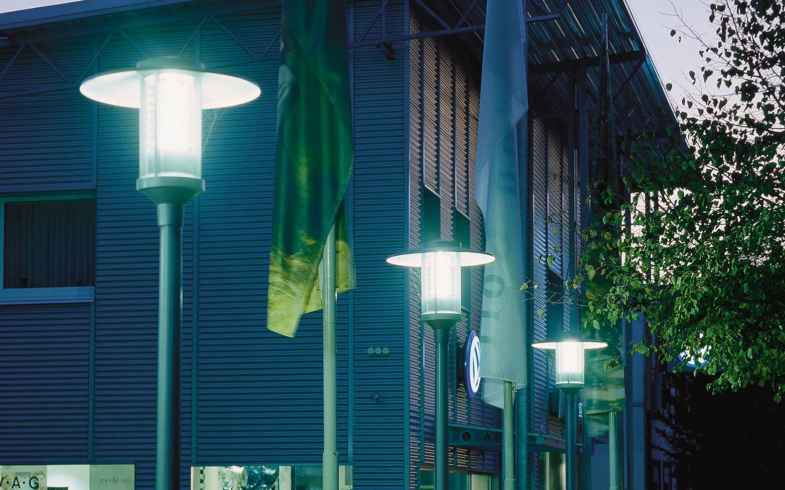 Several lanterns are lined up at a car dealership parking space.