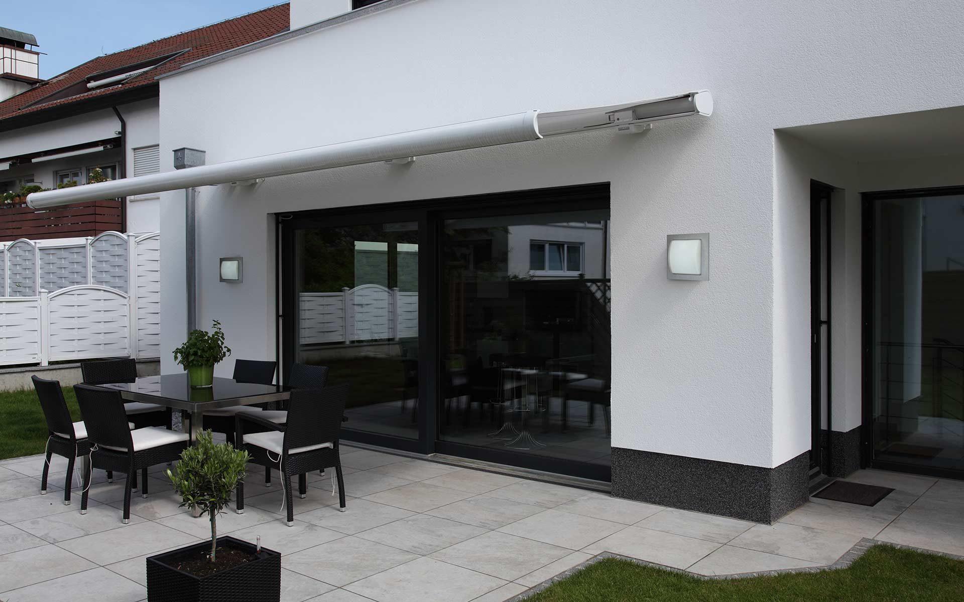 Eine moderne Terrasse mit einer Markise wird durch zwei Albert-Wandleuchten optisch ergänzt.