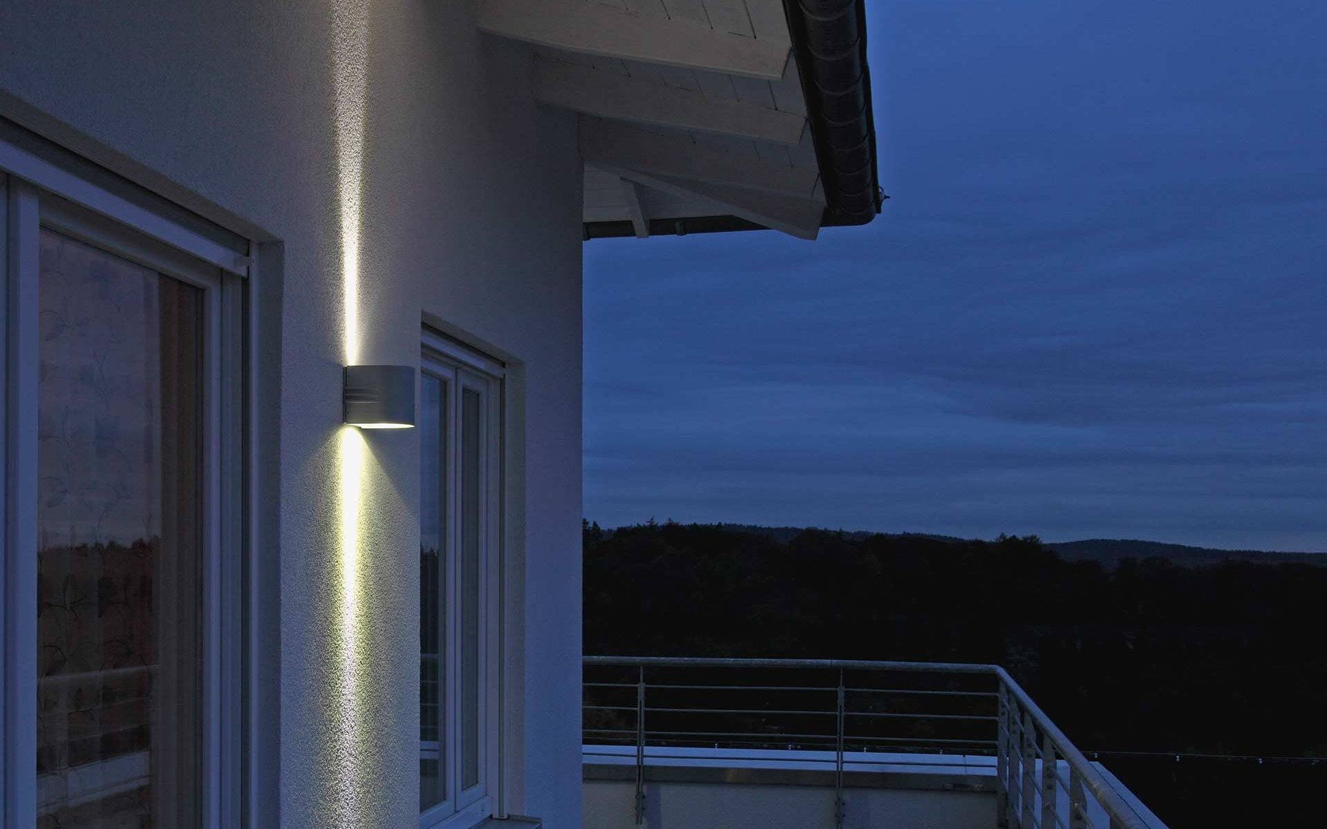 A wall lamp with double-sided light output stylishly sets off a balcony.