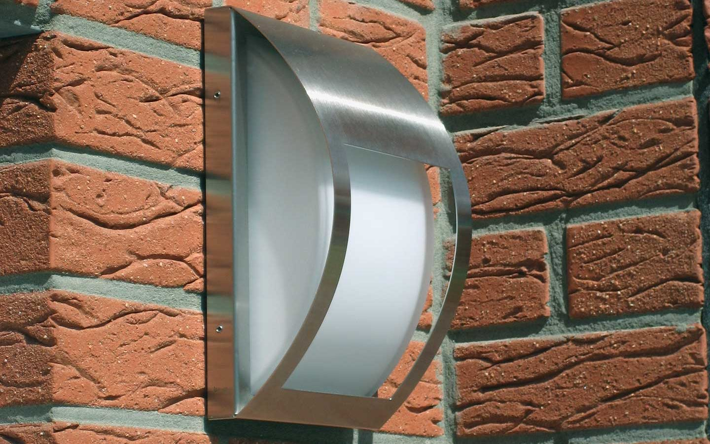 Close-up of a modern stainless steel wall lamp at a house entrance.