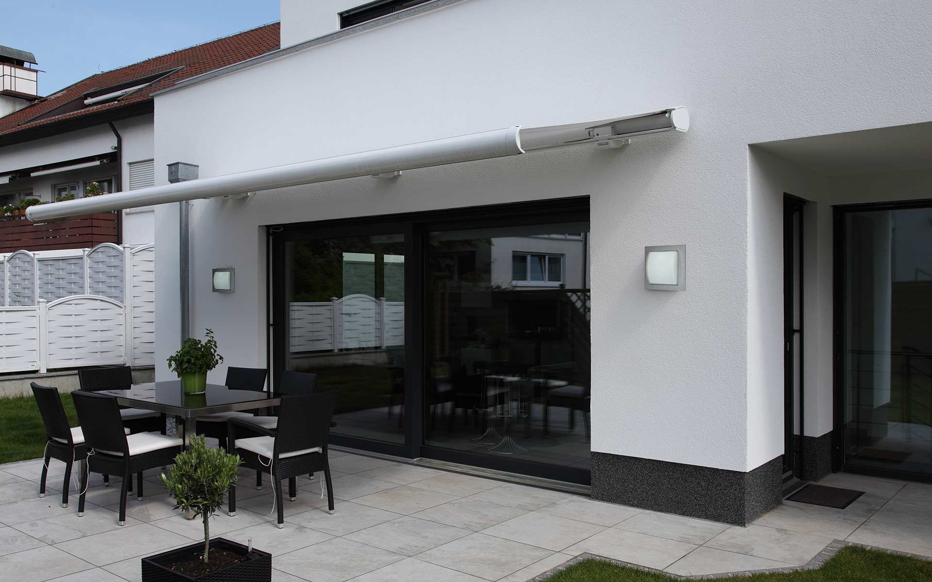 A modern terrace with an awning is visually completed by two Albert wall lights.
