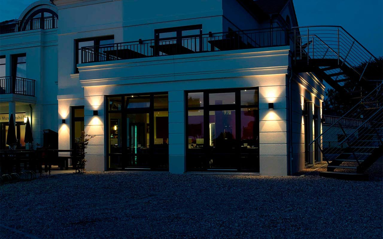 A multi-storey villa is stylishly illuminated by two wall lights at dusk.