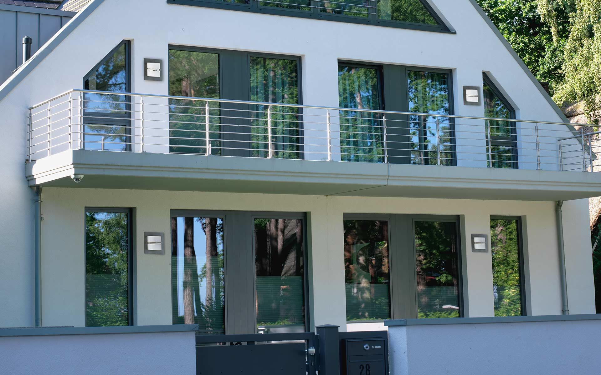 A modern house with balcony and four geometrically arranged wall lights.