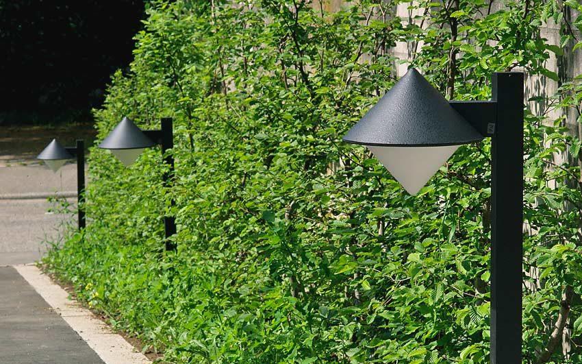 Klassisch gestaltete Wegeleuchten stehen an einem Grünstreifen in Reih und Glied.